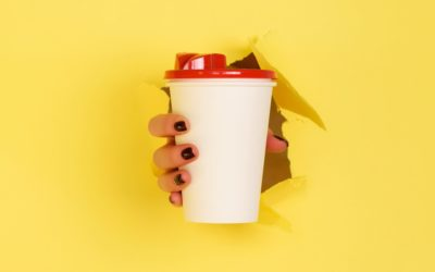 Female hand holding white paper mug on yellow background. Take away coffee cup concept. Mock up with